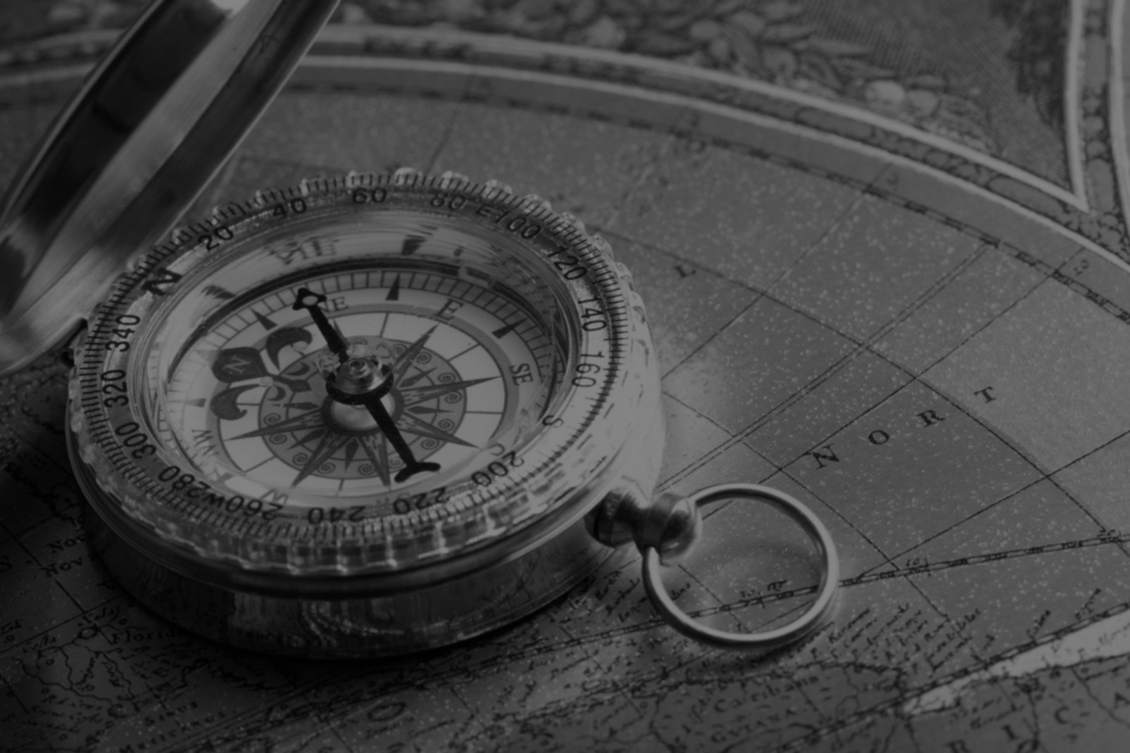A beautiful compass sitting on an antique map